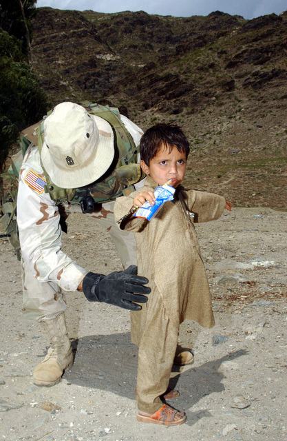 US Army (USA) First Sergeant (1SG) Noll, assigned to 2nd Battalion, 265th Air Defense Artillery (ADA), Florida (FL) Army National Guard (ANG) searches an Afghani boy before he sees an Army Doctor during a Cooperative Medical Assistance (CMA) Program located in the Kunar Province in Afghanistan. Soldier assigned to the 2/265th ADA are providing security and police-related duties for the Asadabad Provincial Reconstruction Team (PRT), Task Force Victory, and Task Force 325 during in Afghanistan, during Operation ENDURING FREEDOM