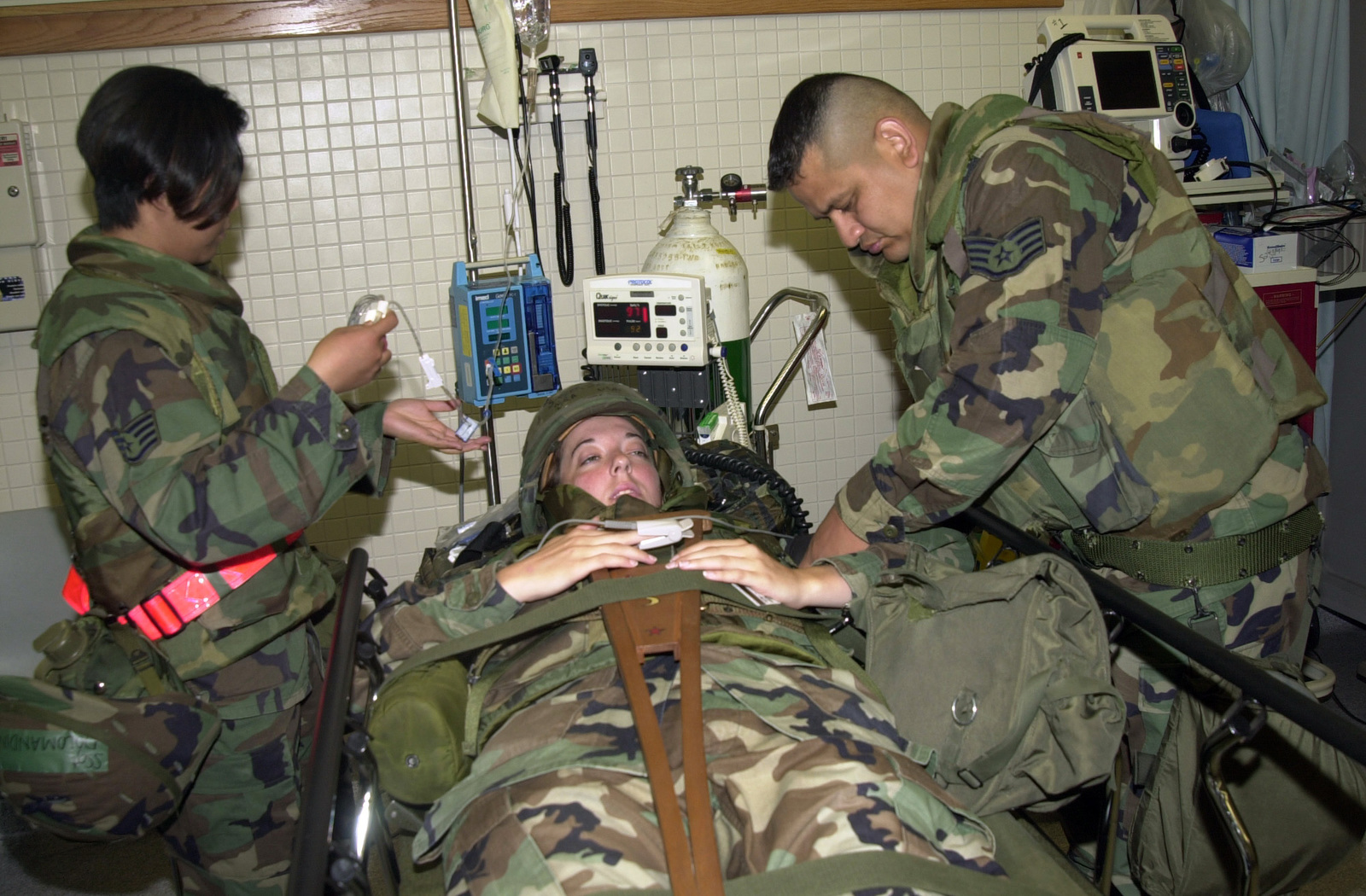 "US Air Force (USAF) STAFF Sergeant (SSGT) Raul Romero (right) and USAF SSGT Konny Dolomandin, both members of the 8th Medical Support Squadron (MSS), treat USAF SENIOR AIRMAN (SRA) Jillian Sasser of the 8th Services Squadron (SS) for""injuries""during Exercise Beverly High 04-04 at Kunsan Air Base (AB), Korea (ROK)"