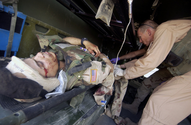 US Army (USA) Sergeant (SGT) John Foxworthy (right), Medical Technician from the 45th Medical Brigade, checks the condition of a Soldier injured during a rocket attack in Baghdad, Iraq, during Operation IRAQI FREEDOM