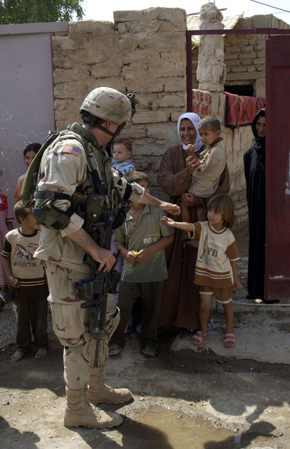 U.S. Army 1ST LT. Merrill, Charlie Company, 2nd Battalion, 108th Infantry Regiment, New York National Guard (NYANG), passes out candy to eager children in the town of Alalaa, Salah al-Dein Province, Iraq, on Aug. 24, 2004.  LT. Merrill is carrying the M4 Carbine assault rifle with a 40 mm M203 grenade launcher attached. (U.S. Army photo by SGT. April L. Johnson) (Released)