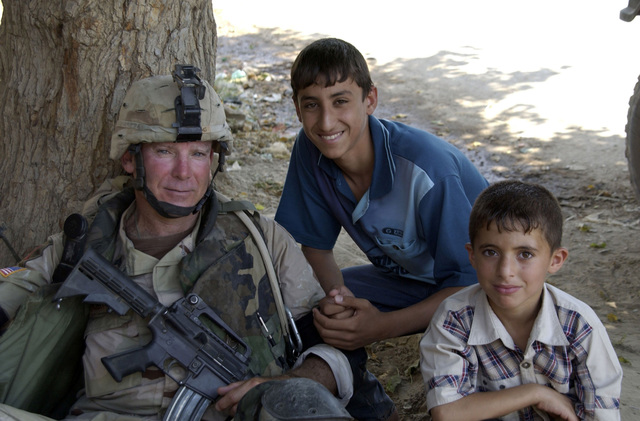 U.S. Army SGT. 1ST Class Forbes (left), Charlie Company, 2nd Battalion, 108th Infantry Regiment, New York National Guard (NYANG), poses for a picture with local children in the town of Alalaa, Salah al-Dein Province, Iraq, on Aug. 24, 2004, during Operation Iraqi Freedom.  (U.S. Army photo by SGT. April L. Johnson) (Released)