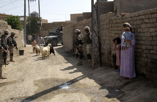 U.S. Army Soldiers, Charlie Company, 2nd Battalion, 108th Infantry Regiment, New York National Guard (NYANG), provide security in an alleyway during a cordon and search in the town of Alalaa, Salah al-Dein Province, Iraq, on Aug. 24, 2004, in support of Operation Iraqi Freedom. (U.S. Army photo by SGT. April L. Johnson) (Released)