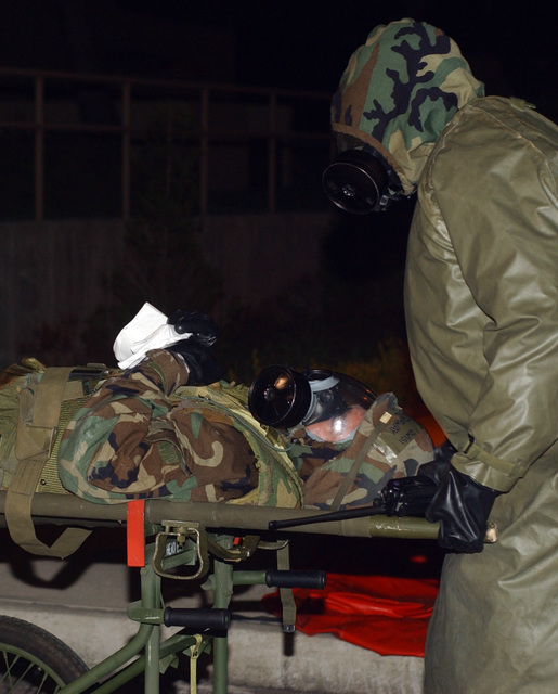 """040824-F-6123A-002 (Aug. 24, 2004)A US Air Force (USAF) AIRMAN from the 8th Medical Group (MG) transport an""""injured patient""""to a decontamination tent following a simulated chemical attack during an Operational Readiness Exercise (ORE) named Beverly High 04-04 at Kunsan Air Base (AB), Korea (KOR). The Airmen are attired in Mission Oriented Protective Posture (MOPP) gear.U.S. Air Force official photo by SENIOR AIRMAN Araceli Alarcon (RELEASED)"""