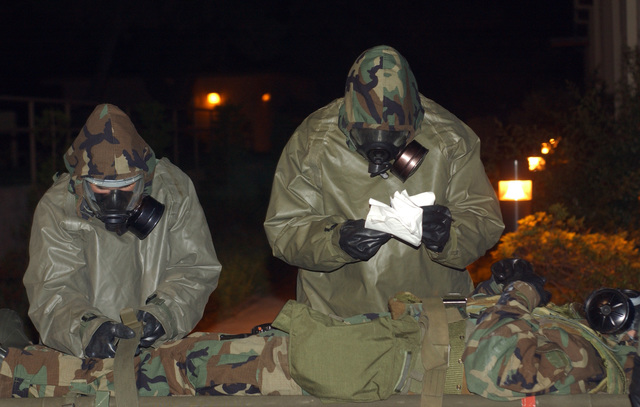 """040824-F-6123A-003 (Aug. 24, 2004)A US Air Force (USAF) Airmen from the 8th Medical Group (MG) prepare to transport an""""injured patient""""to a decontamination tent following a simulated chemical attack during an Operational Readiness Exercise (ORE) named Beverly High 04-04 at Kunsan Air Base (AB), Korea (KOR). The Airmen are attired in Mission Oriented Protective Posture (MOPP) gear.U.S. Air Force official photo by SENIOR AIRMAN Araceli Alarcon (RELEASED)"""