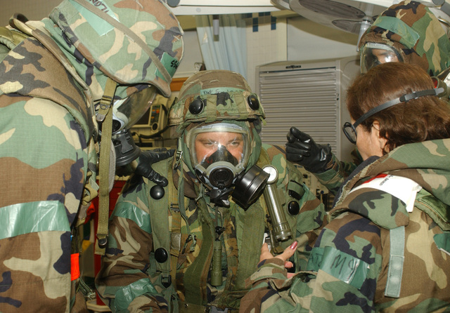 """040824-F-6123A-009 (Aug. 24, 2004)A US Air Force (USAF) Airmen from the 8th Medical Group (MG) examines a""""patient""""for sympstoms from shock at a decontamination tent following a simulated chemical attack during an Operational Readiness Exercise (ORE) named Beverly High 04-04 at Kunsan Air Base (AB), Korea (KOR). The Airmen are attired in Mission Oriented Protective Posture (MOPP) gear.U.S. Air Force official photo by SENIOR AIRMAN Araceli Alarcon (RELEASED)"""