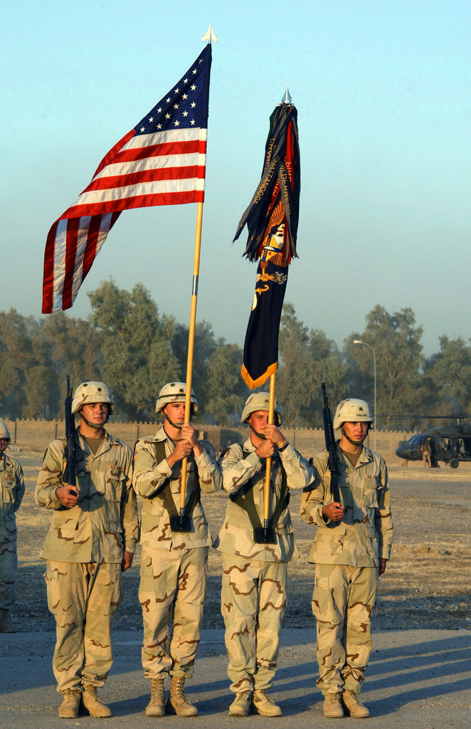 U.S. Army SPEC. Ellis (left), SGT. Archamrault, SGT. Tomko, and SGT. Phillips (right), all assigned to 2nd Battalion, 2nd Infantry Regiment, 3rd Brigade, 1ST Infantry Division, perform Color Guard duties at the Combat Infantry Badge pinning ceremony at Forward Operating Base (FOB) Normandy, Diyala Province, Iraq, on Aug. 25, 2004, during Operation Iraqi Freedom. (U.S. Army photo by PVT. 1ST Class Elizabeth Erste) (Released)