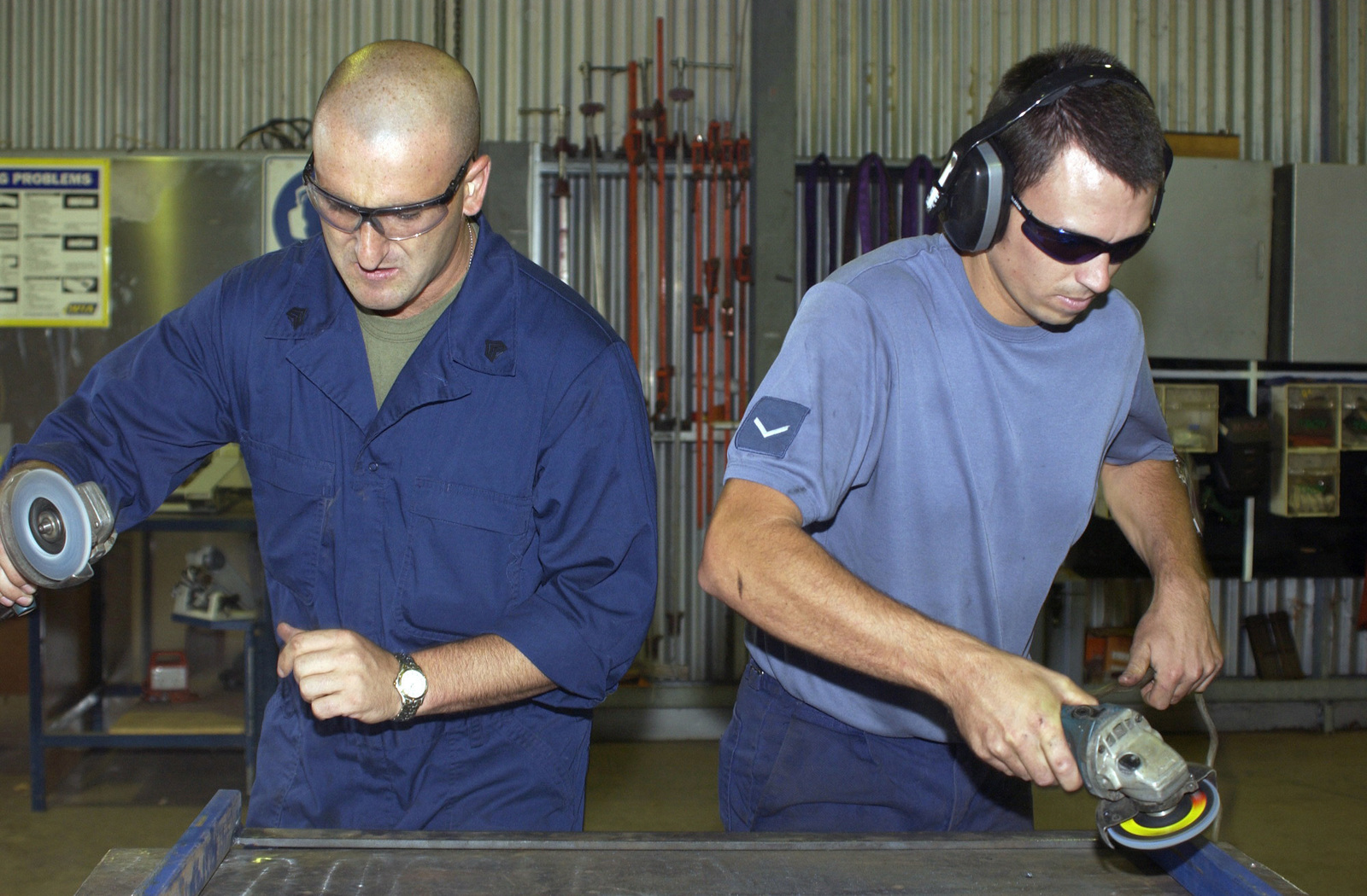 US Marine Corps (USMC) Sergeant (SGT) Steve Hamilton (left), Assistant Maintenance CHIEF, Aircraft Recovery, and a Royal Australian Air Force (RAAF) Airmen use handheld metal grinders while working inside the aircraft maintenance shop at Royal Australian Air Force Base (RAAFB) Tindal, Australia, during Exercise SOUTHERN FRONTIER. The exercise is a combined exercise with the US Marine Corps (USMC) and the Australian military