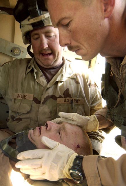 US Army (USA) Sergeant (SGT) John Foxworthy (foreground right), Medical Technician, 45th Medical Brigade, checks an injured USA.  The soldier was hurt in a high-speed car accident on the streets of Baghdad, Iraq, during Operation IRAQI FREEDOM