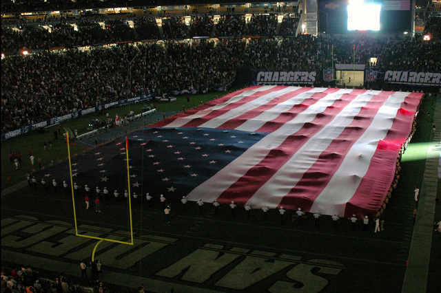 US Navy (USN), US Coast Guard (USCG) and US Marine Corps (USMC) Service members display a large American Flag as part of a Military Appreciation Night program, during the half time intermission of a game between the San Diego Chargers and Seattle Seahawks, from the National Football League (NFL), at Qualcomm Stadium, in San Diego, California (CA)