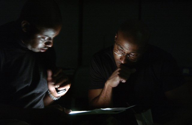 Using flashlights due to the loss of electrical power U.S. Air Force Technical Sergeants Anthony Morris and Federick Toone, make a list of available personnel to help establish operational readiness at Patrick Air Force Base, Fla.  The sergeants are part of the 45th Hurricane Recovery Team assigned to Patrick and responsible for securing and establishing flight operations once Hurricane Frances moves through central Florida. The 57-member team weathered the effects of Frances, the largest storm recorded, to date, to hit the state, at an Air Force annex located southwest of Patrick in the town of Malabar, Fla. (U.S. Air Force photo by MASTER Sergeant Efrain Gonzalez) (Released)