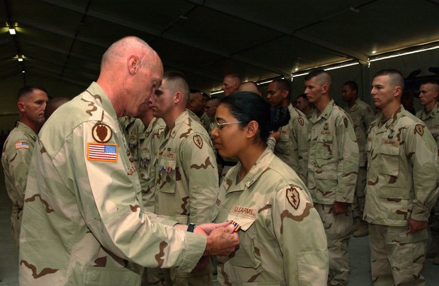 U.S. Army GEN. Eric T. Olson (left), Commander, Combined Joint Task Force 76 and 25th Infantry Division (Light), pins the Global War on Terrorism Service Medal on PVT. 1ST Class Olivia Torres, 125th Signal Battalion, 25th Infantry Division (Light), at Kandahar Airfield, Afghanistan, on Sept. 6, 2004, during a Combat Unit Patch ceremony. (U.S. Army photo by SPEC. Jerry T. Combs) (Released)