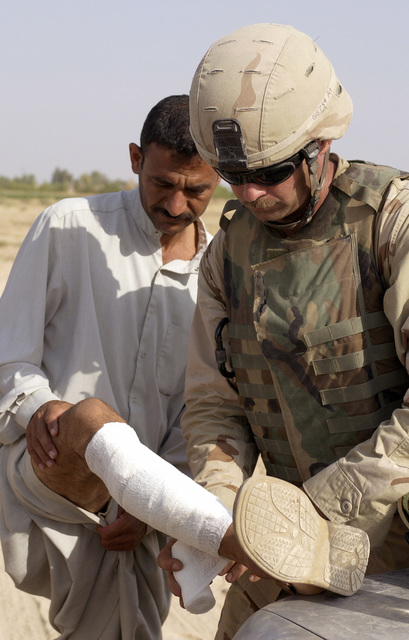 California Army National Guard SGT. Robert Harms Bravo Company, 1ST Battalion, 185th Armor, 81st Armor Brigade, applies first aid to a local Iraqi during a random car search checkpoint on Sept. 7, 2004 around Balad, Iraq, during Operation Iraqi Freedom. The car searches are to deny anti-Iraqi forces the freedom to operate and move throughout the countryside. (U.S. Air Force photo by STAFF Sergeant Shane A. Cuomo) (Released)