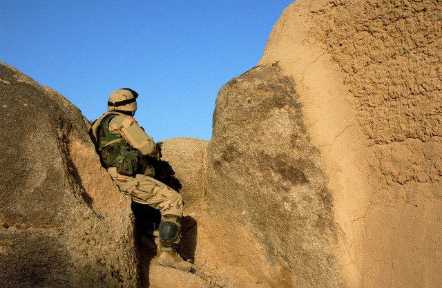 A U.S. Army Soldier, 3rd Platoon, Charlie Company, 2nd Battalion, 35th Infantry Regiment, 25th Infantry Division, holds a position alongside the face of a rock at Forward Operating Base (FOB) Tiger, Afghanistan, armed with an M4 Carbine assault rifle on Sept. 8, 2004, during a security halt while on a search of the mountain ranges. (U.S. Army photo by STAFF SGT. Joseph P. Collins, Jr.) (Released)