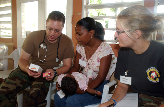 U.S. Air Force LT. COL. Clay Walsh (left), a Medical Doctor assigned to the 179th Medical Squadron, tells a mother how medication is to be administered to her baby, during a Dominican Republic Humanitarian Civic Actions Program, at Dajabon, Dominican Republic, on September 8, 2004. The 179th set up mobile clinics in four towns during 10-days. The clinics treat medical, dental, eye patients and have a pharmacy.  Assisting the Doctor is SENIOR AIRMAN Nicole Feix (right). (U.S. Air Force photo by TECH. SGT. Robert Jones) (Released)
