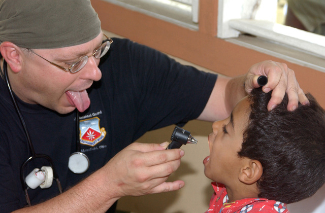 U.S. Air Force LT. COL. Clay Walsh (left), a medical doctor assigned to the 179th Medical Squadron, encourages a young patient during an examine at a free clinic during a Dominican Republic Humanitarian Civic Actions Program, at Dajabon, Dominican Republic, on September 8, 2004. The 179th set up mobile clinics in four towns during 10-days. The clinics treat medical, dental, eye patients and have a pharmacy. (U.S. Air Force PHOTO by TECH. SGT. Robert Jones) (Released)