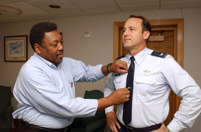 Mr. Roy Crear, from the Multi Media Center Presentations Division, 42nd Communications Squadron, attaches a remote microphone tie clip on U.S. Air Force COL. Tom Jones, Commander, 42nd Squadron Officers College, prior to the start of the Air and Space Basic Course, Class of 2004-F Briefing, being held at the Squadron Officers School, at Maxwell Air Force Base, Ala., on September 9, 2004. U.S. Air Force PHOTO by Melanie Rodgers) (Released)