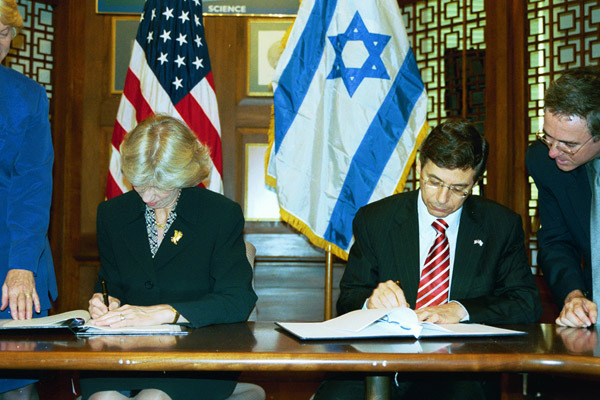 Secretary Gale Norton, seated left, and Israel's Ambassador to the U.S., Daniel Ayalon, seated right, applying signatures during Department of Interior headquarters signing ceremony for agreement expanding scientific and technical cooperation, between the Department of Interior and Israel's Ministry of National Infrastructures, across a range of natural resource management areas