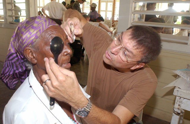 U.S. Air Force LT. COL. Kenneth Vanderzeyde (left) assigned to the 179th Medical Squadron tests different lens combinations on a woman in need of glasses, during an examine at a free clinic, during a Dominican Republic Humanitarian Civic Actions Program, at Dajabon, Dominican Republic, on September 9, 2004. The 179th set up mobile clinics in four towns during 10-days. The clinics treat medical, dental, eye patients and have a pharmacy. (U.S. Air Force PHOTO by TECH. SGT. Robert Jones) (Released)d)