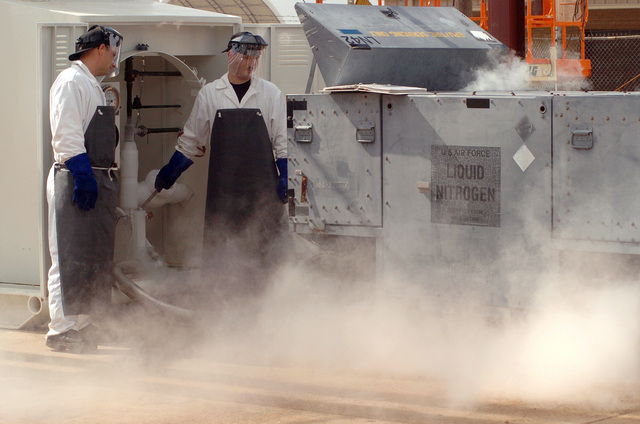 U.S. Air Force STAFF SGT. Brian Clevenger and STAFF SGT. James Wittkofski, both assigned to the 20th Logistics Readiness Squadron, refill liquid oxygen containers at the cryogenics tanks, at Shaw Air Force Base, S.C., on September 9, 2004.  (U.S. Air Force PHOTO by MASTER SGT. Paul Holcomb) (Released)