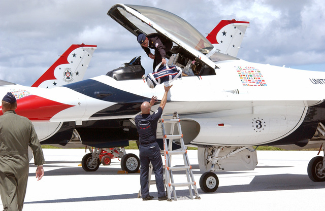 U.S. Air Force TECH. SGT. Brian Plauche, a Crew CHIEF assigned to the U.S. Air Force Thunderbirds Aerial Demonstration Team, helps MAJ. Brian Burns out of his F-16C Fighting Falcon aircraft on the flight line at Andersen Air Force Base, Guam, September 9, 2004.  This landing marks the first time in a decade the Thunderbirds Demonstration Team has visited Guam. The Thunderbirds will be performing during an air show held Sunday, September 12, 2004. (U.S. Air Force PHOTO by AIRMAN 1ST Class Kristin Ruleau) (Released)