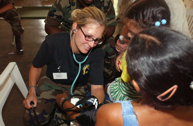 U.S. Aircraft SENIOR AIRMAN Nicole Feix, assigned to the 197th Medical Squadron, takes the blood pressure on a young patient during a Humanitarian Civic Action Program in Dajabon, Dominican Republic, on September 10, 2004. The 179th set up mobile clinics in four towns during 10-days. The clinics treat medical, dental, and eye patients and have a pharmacy equipped with donated medical supplies and medicines. (U.S. Air Force PHOTO by TECH. SGT. Robert Jones) (Released)