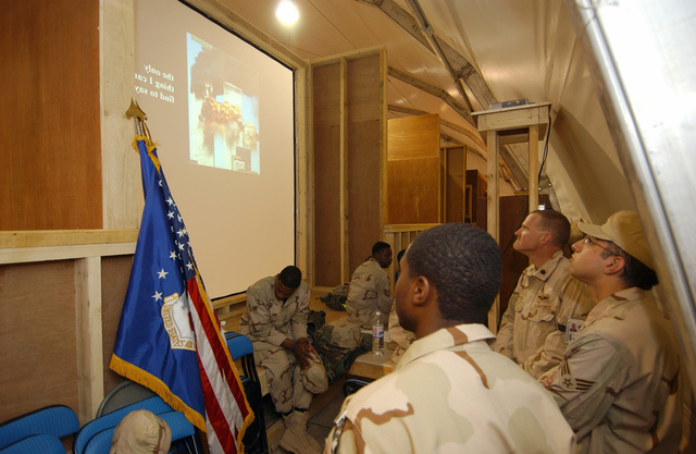 U.S. Air Force Airmen assigned to the 332nd Air Expeditionary Wing, watch a tribute of photographs dedicated for the 9/11 Memorial Service held at the Balad Town Hall at Balad Air Base, Iraq, on September 11, 2004. (U.S. Air Force PHOTO by TECH. SGT. Rob Jensen) (Released)