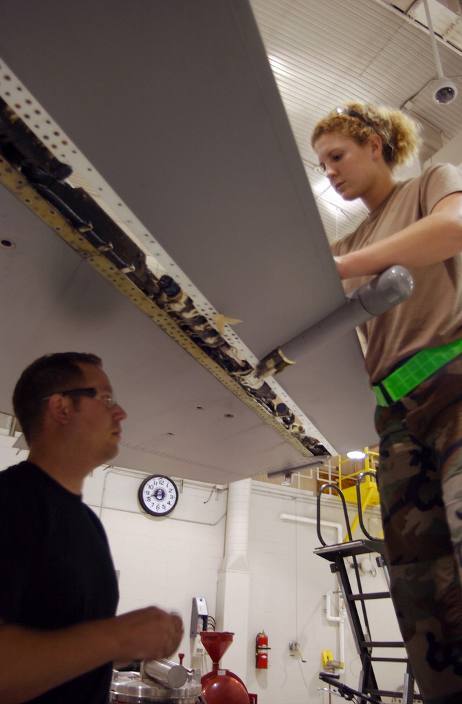 U.S. Air Force STAFF SGT. Eric Young (left) and SENIOR AIRMAN Ariel Keating, both assigned to the Sheet Metal Section, 114th Fighter Wing, work on the wing of a F-16C Fighting Falcon aircraft in the corrosion control anger at Joe Foss Field, Sioux Falls, S. D., on Sept. 11, 2004. (U.S. Air Force PHOTO by STAFF SGT. Mike Frye) (Released)