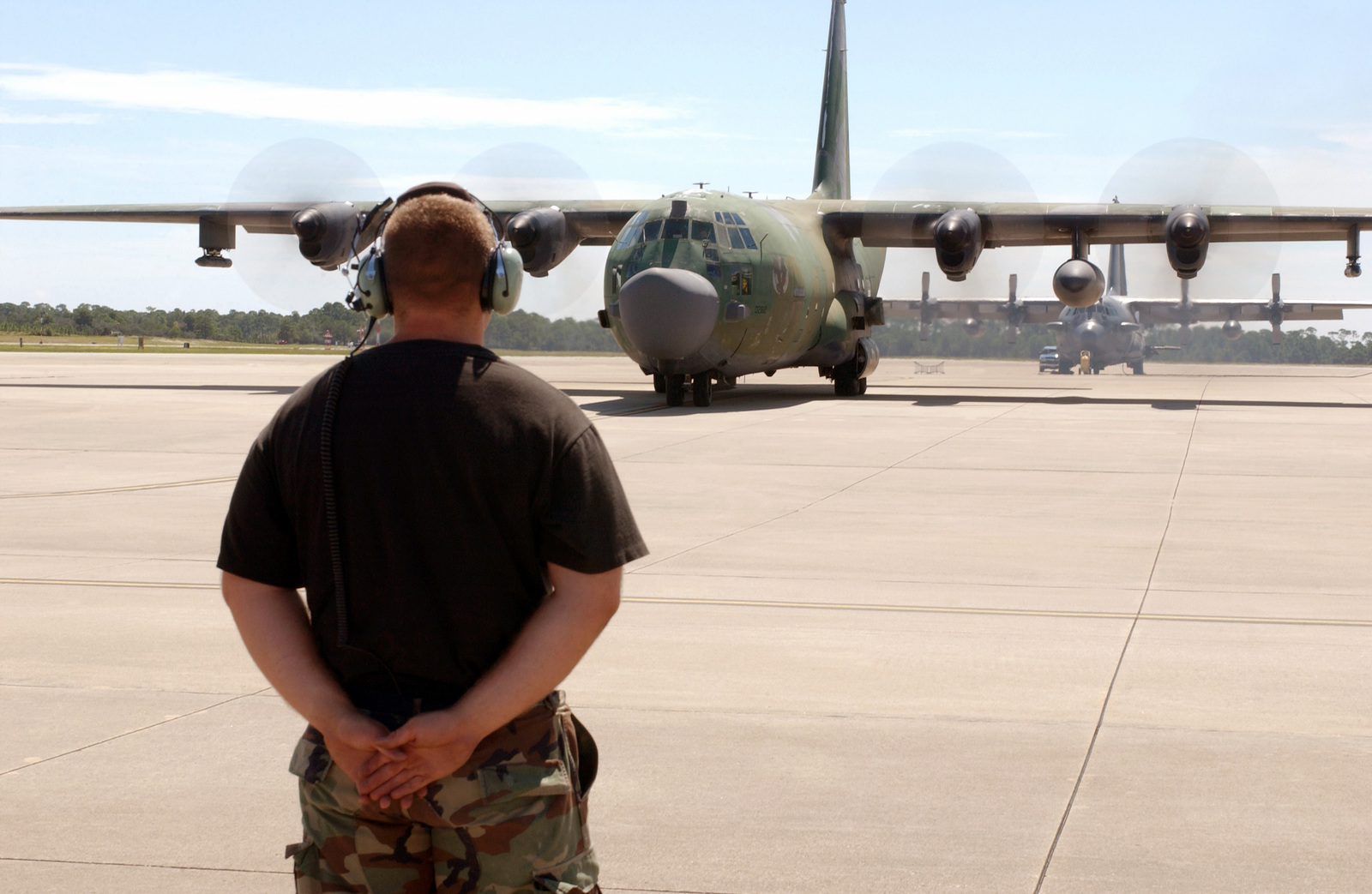 U.S. Air Force STAFF SGT. Adam Smith assigned to the 16th Special Operations Wing, marshals a MC-130H Talon aircraft onto the tarmac as it prepares to leave Hurlburt Field, Fla, as part of the Advanced Contingency Team leaving for Fort Campbell, Kentucky on Sept. 12, 2004, in preparation for Hurricane Ivan. (US Air Force PHOTO by AIRMAN 1ST Class Kimberly Gilligan) (Released)
