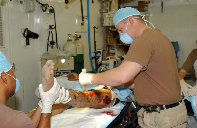 U.S. Army SPEC. Richard Crane (right), Surgical Technician, and STAFF SGT. Jorge Solis, both from 325th Field Surgical Team, prepares a local national who was shot in the thigh with an AK-47 assault rifle for surgery at Kandahar Airfield, Afghanistan, on Sept. 12, 2004, in support of Operation Enduring Freedom. (U.S. Army photo by STAFF SGT. Joseph P. Collins, Jr.) (Released)