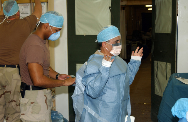 U.S. Army STAFF SGT. Jorge (foreground, left), assists COL. Richard Gonzalez, Medical Doctor, with his surgical attire as they prepare for surgery on a local national who was shot in the thigh with an AK-47 assault rifle at Kandahar Airfield, Afghanistan, on Sept. 12, 2004, in support of Operation Enduring Freedom. (U.S. Army photo by STAFF SGT. Joseph P. Collins, Jr.) (Released)