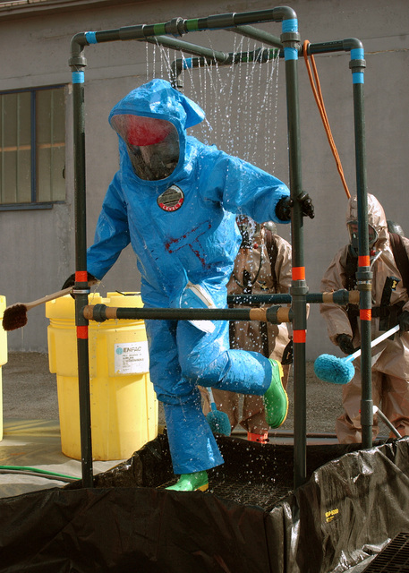 A U.S. Air Force member with the 31st Civil Engineer Squadron, hazard material, Aviano Air Base, Italy, decontaminates himself after leaving a potential gas contaminated area during a mass casualty exercise simulating a terrorist attack at a local shopping district in Roveredo in Piano, Italy, on Sept. 13, 2004.(U.S. Air Force PHOTO by AIRMAN 1ST Class Scherrie Gates) (RELEASED)