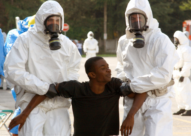 Italian Police carry U.S. Air Force SENIOR AIRMAN Kevin Alexander, 31st Logistics Readiness Squadron, Aviano Air Base, Italy, to a decontamination shower during a mass casualty exercise, simulating a terrorist attack in Roveredo in Piano, Italy, on Sept. 13, 2004.(U.S. Air Force PHOTO by SENIOR AIRMAN Nichole Adamowicz)  (RELEASED)