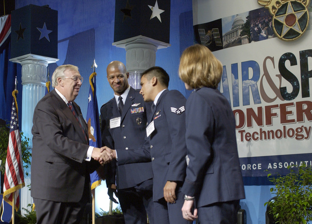 The Honorable Secretary of the Air Force Dr. James G. Roche congratulates U.S. Air Force SENIOR AIRMAN Tranquilino Herrera, loadmaster, 7th Airlift Squadron, McChord Air Force Base, Wash., for his feature in U.S. Air Force commercials, as MAJ. Rodney Stephan, second left, a B-1B Pilot, Dyess Air Force Base, TX, and CAPT. Morgan Bailey-Johnson, program manager, military satellite communications and ground control systems, Los Angeles Air Force Base, Calif., right, look on at the Air Force Association's 2004 Air and Space Conference and Technology Exposition at Washington, D.C., on Sept. 13, 2004. (U.S. Air Force photo by MASTER SGT. Jim Varhegyi) (Released)