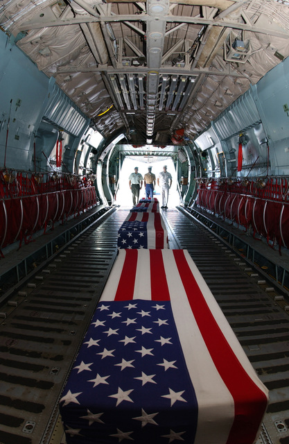Left to right: U.S. Army, STAFF SGT. Steven Robles, U.S. Marine Corps SGT. Anthony Riley, and U.S. Navy, Cryptologic Technician 3rd Class, Vincent Nguyen, Joint Honor Guard, standing at the tail end of a C-141 Starlifter cargo aircraft, with the remains of repatriated American warriors from the Korean War and World War II at Hickam Air Force Base, Hawaii, on Sept. 14, 2004.(U.S. Air Force PHOTO by Mysti Bicoy, CIV.) (RELEASED)