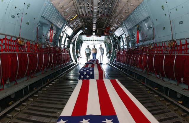 Left to right: U.S. Army, STAFF SGT. Steven Robles, U.S. Marine Corps SGT. Anthony Riley, and U.S. Navy, Cryptologic Technician 3rd Class, Vincent Nguyen, stand at the tail end of a C-141 Starlifter cargo aircraft, with the remains of repatriated American warriors from the Korean War and World War II at Hickam Air Force Base, Hawaii, on Sept. 14, 2004.(U.S. Air Force PHOTO by Mysti Bicoy, CIV.) (RELEASED)