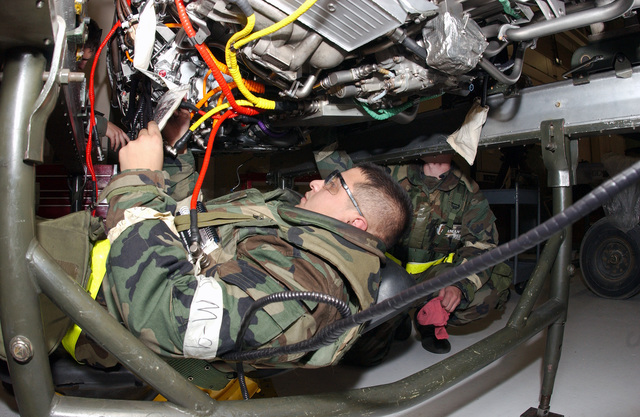 U.S. Air Force SENIOR AIRMAN Felipe Venegas, 354th Maintenance Squadron, 354th Fighter Wing, installs an electrical harness on a F-16 Fighting Falcon fighter aircraft engine, while in Mission Oriented Protective Posture level 2, during an Operational Readiness Exercise Phase 2 at Eielson Air Force Base, Alaska, on Sept. 14, 2004.(U.S. Air Force PHOTO by SENIOR AIRMAN Joshua Strang) (RELEASED)