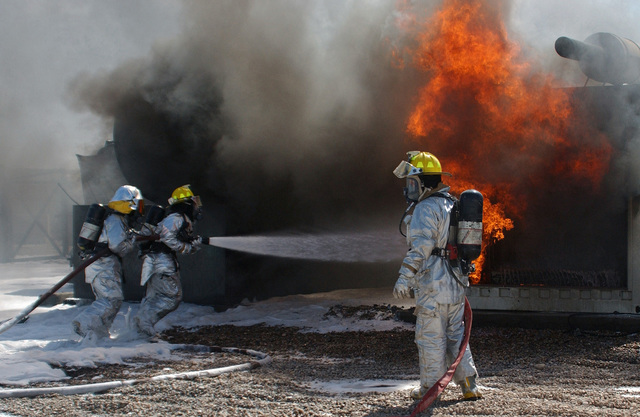 US Air Force (USAF) Firefighter assigned to the 506th Civil Engineering Squadron (CES) respond to a fuel spill fire at the dining facility at Kirkuk AB, Iraq, during Operation IRAQI FREEDOM. A fire started near the dining facility when a fuel truck was pumping fuel to a fuel tank and a spark triggered the fire