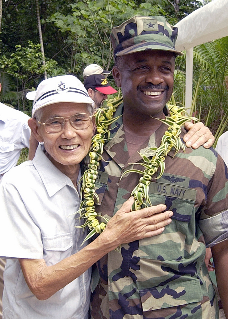 Mr. Kiyokazu Tsuchida (left), a former World War II (WWII) Japanese Army Soldier, and US Navy (USN) Rear Admiral (RADM) Arthur J. Johnson, Commander, US Naval Region Marianas, meet and embrace during a ceremony commemorating the 60th Anniversary of the Battle of Peleliu, held at Peleliu Island, Guam. Mr. Tsuchida, who was stationed on the island in 1944 hid in the Islands cave and jungles for nearly two years after the war ended and did not surrender to American forces until April 1947