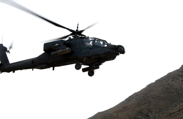 A US Army (USA) AH-64 Apache helicopter assigned to B/Company, 2-211th Aviation Regiment refuels at the Asadabad, Landing Zone, provides security while ballots from the first-ever democratic national presidential election, are loaded onto a waiting helicopter, during Operation ENDURING FREEDOM