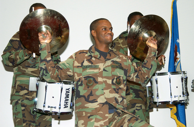 U.S. Air Force SENIOR AIRMAN Davidson Lawrence, 62nd Civil Engineer Squadron, holds the cymbals for snare drummers MASTER SGT. Steven Crowell (left) and SENIOR AIRMAN Seth Miller (right), as part of a drumline before the 62nd Mission Support Group, quarterly awards ceremony at McChord Air Force Base, Wash., on Sept. 16, 2004.(U.S. Air Force PHOTO by Kristin Royalty, CIV.) (RELEASED)