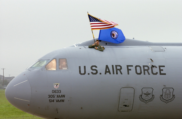 U.S. Air Force SENIOR MASTER SGT. Thomas Kenny, 6th Airlift Squadron, displays the American and 6th Airlift Squadron flag aboard the final C-141B Starlifter cargo aircraft, number 0633, to depart McGuire Air Force Base, N.J. for the Aerospace Maintenance and Regeneration Center, Davis-Monthan Air Force Base, Ariz., on Sept. 16, 2004.(U.S. Air Force PHOTO by Scott H. Spitzer, CIV.) (RELEASED)