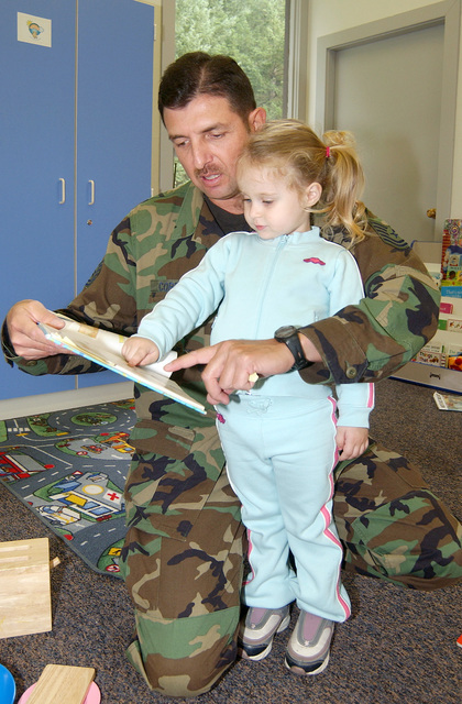U.S. Air Force volunteer TECH. SGT. Chris Cordero, 62nd Medical Support Squadron, reads a bilingual children's book to two-year-old Kaitlyn Dunn during the Hispanic Heritage Month festivities at McChord AFB, Wash., on Sept. 16, 2004.(U.S. Air Force PHOTO by Kristin Royalty, CIV.) (RELEASED)