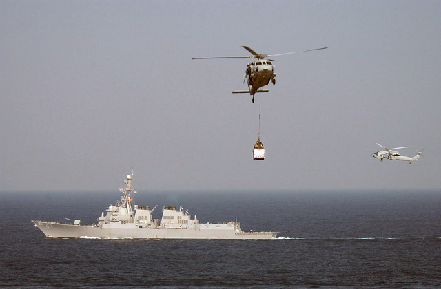 Two US Navy (USN) MH-60S KnightHawk helicopter assigned to Helicopter Combat Support Squadron One One (HC-11) conduct Vertical Replenishment (VERTREP) operations with the Arleigh Burke Class: (Flight IIA) Guided Missile Destroyer (Aegis) USS HOWARD (DDG 83), while the ship is underway conducting a scheduled deployment in the Western Pacific Ocean