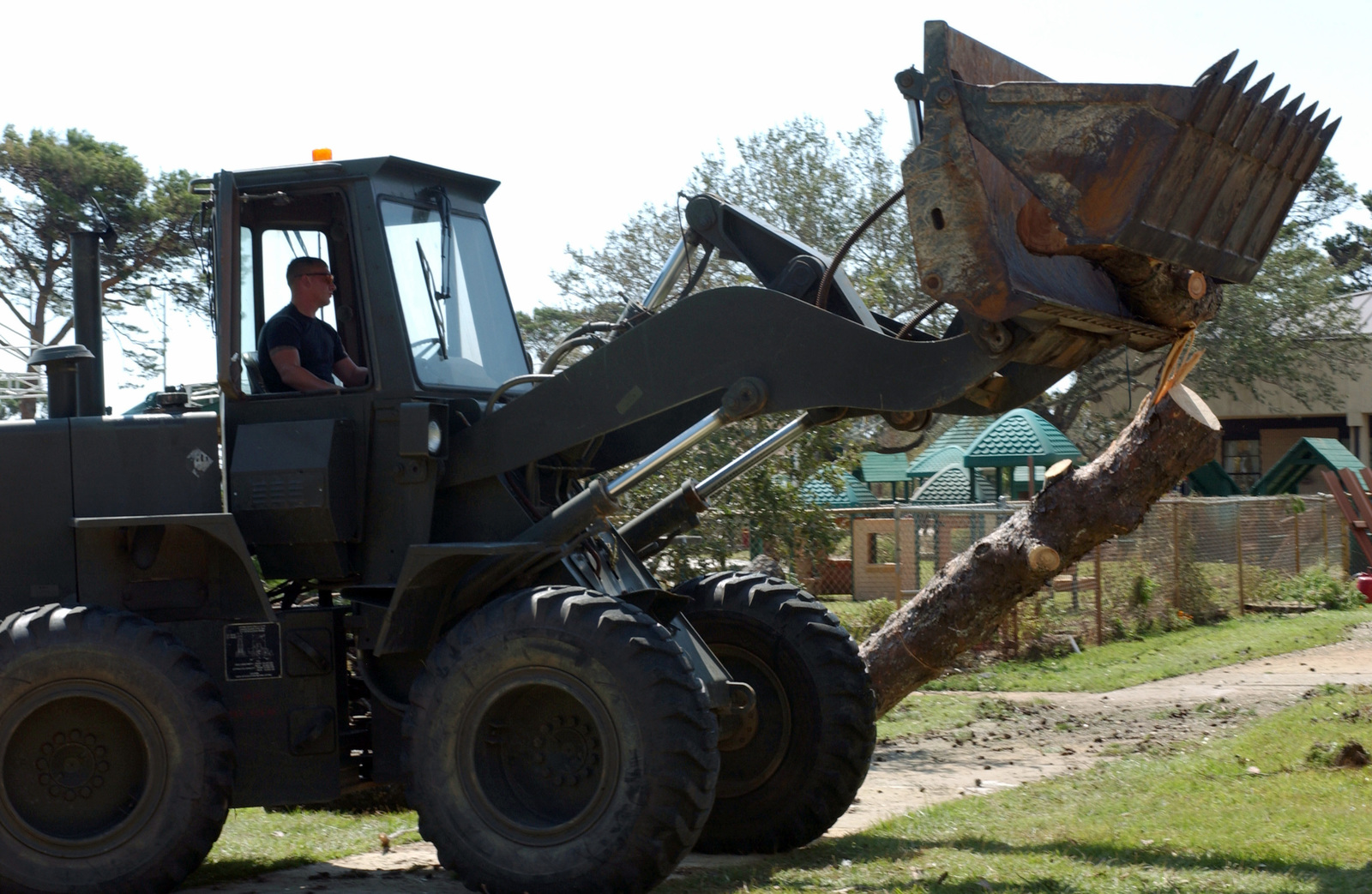 U.S. Air Force STAFF SGT. Bobby Young, 16th Civil Engineering Squadron, uses an International wheel loader to clear fallen trees on Hurlburt Field, Fla., Sept. 19, 2004.  The base has suffered extensive damage after Hurricane Ivan made landfall earlier in the week.   (US Air Force PHOTO by AIRMAN First Class Kimberly Gilligan) (RELEASED)