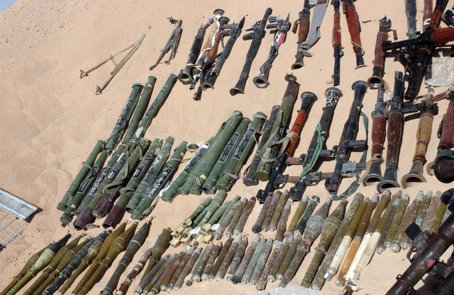 A large number of rocket-propelled grenades (RPG) (bottom), RPG-7 grenade launchers (top) and RPG-18 light anti-armour weapons (center, left), found by Iraqi Security Forces during a raid of a Muqtada al Sadr safe house in An Najaf, An Najaf Province, Iraq, are displayed by U.S. Marine Corps Marines, 11th Marine Expeditionary Unit (MEU) Special Operations Capable, Sept. 21, 2004. These caches were found in different buildings among the city and are in direct violation of the peace agreement between the Grand Ayatollah Sayyid Ali Husaini al-Sistani, highest religious authority and leader of the Hawza (Najaf), and al Sadr, an agreement blessed by the Iraqi Interim Government. The 4th...