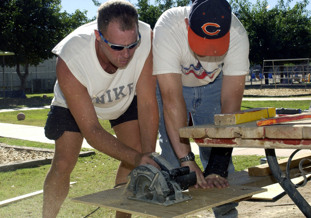 U.S. Air Force TECH. SGT. Robert Ward (left) and USAF STAFF SGT. Charles Ridley, 49th Material Maintenance Group, Holloman Air Force Base, N.M., cut wood to replace the old wood from a children's playhouse at the Zia Therapy Child Development Center on Sept. 23, 2004. The annual Otero County United Way Day of Caring benefits people and organizations needing help because of a handicap or other special need. Over 400 volunteers from Holloman performed work such as grass cutting, painting, pulling weeds, general house keeping, serving meals, and wood work for the local communities near the base. (U.S. Air Force photo by Technical Sergeant James R. Hart Jr.) (Released)