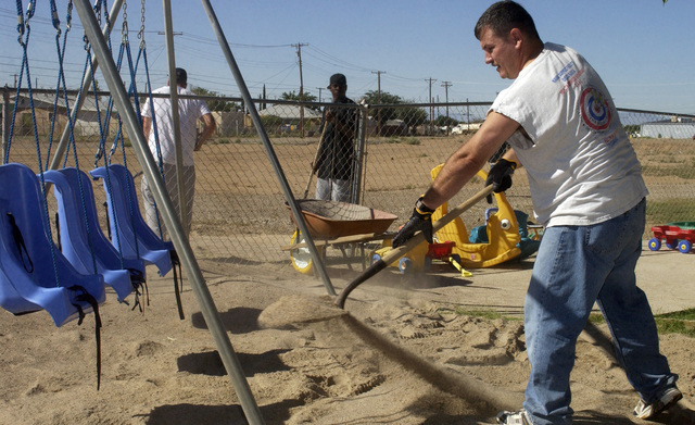 U.S. Air Force TECH. SGT. William C. Miles, 49th Material Maintenance Group, Holloman Air Force Base, N.M., refills sand to a playground swing area at the Zia Therapy Child Development Center on Sept. 23, 2004. The annual Otero County United Way Day of Caring benefits people and organizations needing help because of a handicap or other special need. Over 400 volunteers from Holloman performed work such as grass cutting, painting, pulling weeds, general house keeping, serving meals, and wood work for the local communities near the base. (U.S. Air Force photo by Technical Sergeant James R. Hart Jr.) (Released)