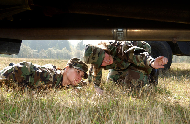 U.S. Air Force CAPT. Jenny Lewis (right) points out to USAF AIRMAN 1ST Class Diana Lafon, a piece of explosive ordnance in the undercarriage of a truck on Sept. 24, 2004. The pair, with the 62nd Medical Group, McChord Air Force Base, Wash., are participating in a training exercise to gain experience identifying unexploded ordnance in their surroundings. (U.S. Air Force photo by Kristin Royalty, CIV) (Released)