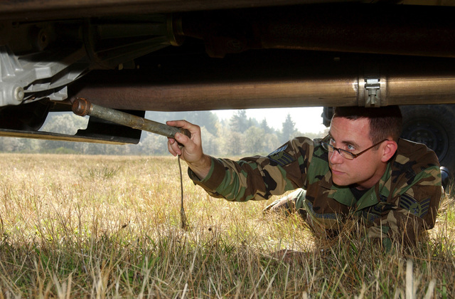 U.S. Air Force STAFF SGT. Robert Whitehurst, 62nd Civil Engineer Squadron, places a mock pipe bomb in the undercarriage of a truck during a demonstration to train Airmen on how to look for and identify ordnances. STAFF SGT Whitehurst, who held the demonstration as part of Ability to Survive and Operate training session, is an explosive ordnance specialist assigned to McChord Air Force Base, Wash. (U.S. Air Force photo by Kristin Royalty, CIV) (Released)