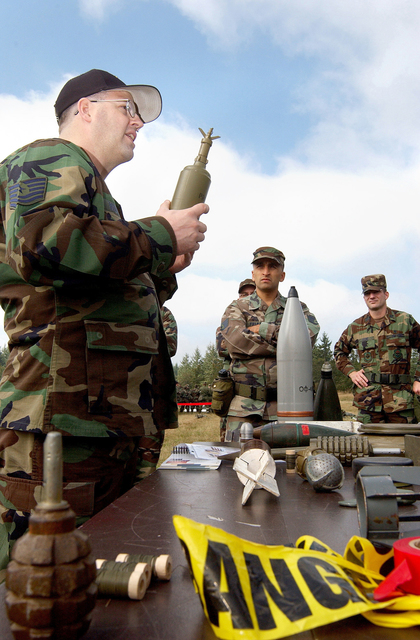 U.S. Air Force TECH. SGT. James Widmark (left), 62nd Civil Engineer Squadron, Explosive Ordnance Disposal Flight, briefs Airmen from the 62nd Medical Group on identifying various explosive ordnances including mortars, grenades, and land mines. The briefing, given during an Ability to Survive and Operate Training session on McChord Air Force Base, Wash., trains Airmen on how to identify and respond to unexploded ordnances. (U.S. Air Force photo by Kristin Royalty, CIV) (Released)